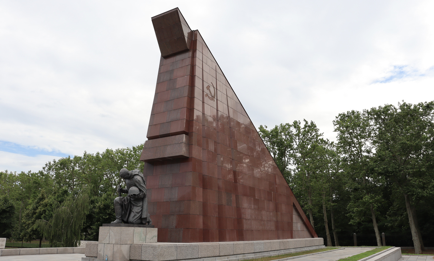 Large red granite flags flank the entrance, a penitent soldier kneels.