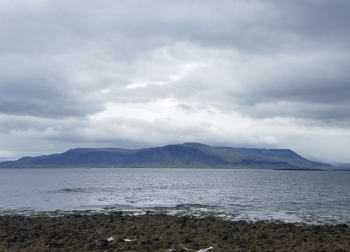 Mountains beyond a bay, under a coming storm